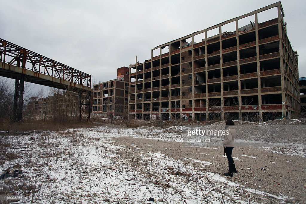 A woman looks at the abandoned Packard Plant December 13, 2013 in Detroit, Michigan. Peru-based developer Fernando Palazuelo made his final payment on the Packard Plant, which he won during a Wayne County auction for $405,000. Palazuelo plans on developing the former automotive plant where luxury Packard cars were made in the coming years.