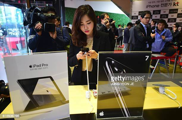 A woman looks at the Apple iPhone 7 at a telecom shop in Seoul on October 21 2016 Apple released for sale its new iPhone 7 and 7 Plus in South Korea...