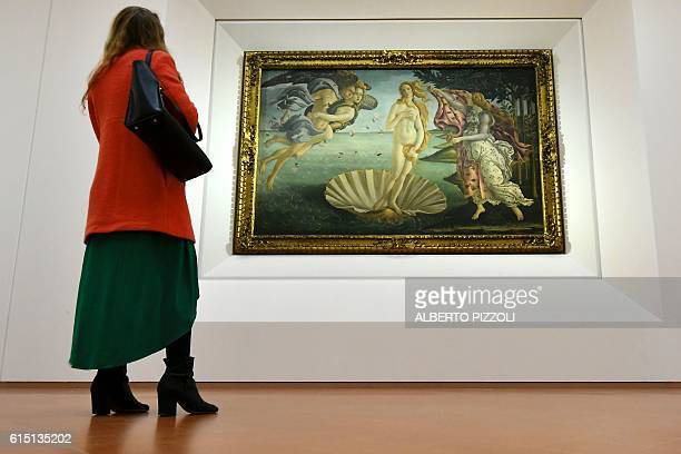 A woman looks at 'The Birth of Venus' painted in 1485 by Italian painter Sandro Botticelli during a press preview for the reopening the rooms...