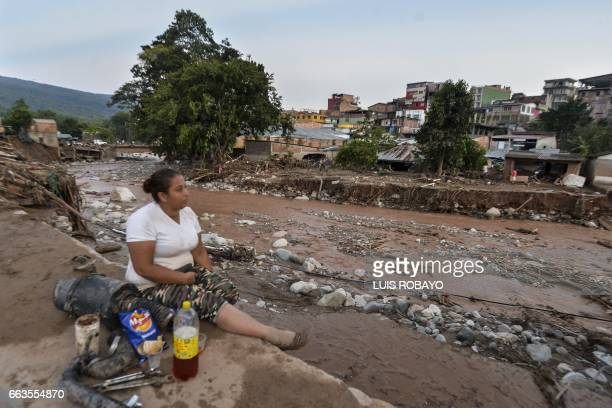 TOPSHOT A woman looks at the damage caused by mudslides following heavy rains in Mocoa Putumayo department southern Colombia on April 1 2017 Massive...