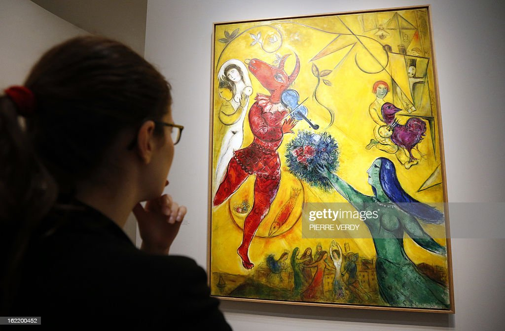 A woman looks at 'The dance' (1950) painting by Russian-born and naturalized French painter Marc Chagall, during an exhibition entitled 'Between war and peace', on February 20, 2013 at the Museum of Luxembourg in Paris. The event will be held from February 21 until July 21, 2013.