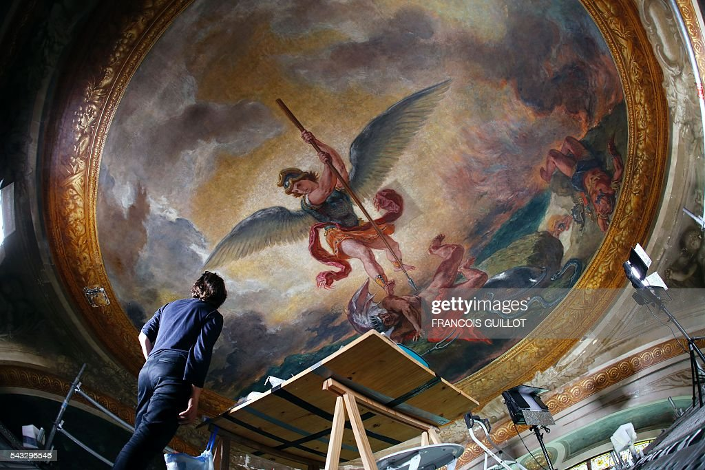 A woman looks at the Eugene Delacroix paintings made between 1849 and 1861 during a restoration at the Saints-Anges chapel inside the Saint-Sulpice church in Paris, on June 27, 2016. / AFP / FRANCOIS