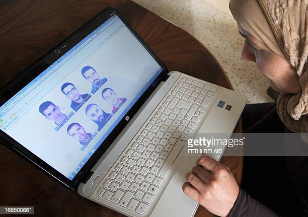 A woman looks at the facebook page of Tunisia's interior ministry on which are published the photos of five Islamists wanted for the assassination in...