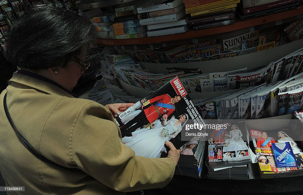 A woman looks at the front cover of Spanish magazine Hola about the marriage of their Royal Highnesses Prince William, Duke of Cambridge and Catherine, Duchess of Cambridge following their wedding the day before, at a newsstand on May 2, 2011 in Madrid, Spain.