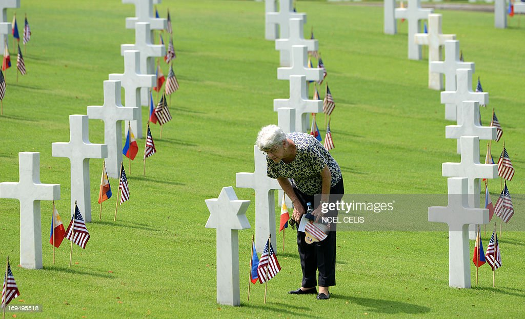A woman looks at the grave of a soldier who fell during World War II, during services to mark US Memorial Day at the Manila American Cemetery in Fort Bonifacio in Manila on May 26, 2013. At least 17,000 graves are in the park that pays tribute to US and Philippines soldiers that fought side-by-side during World War II. The US marks Memorial Day on May 27.