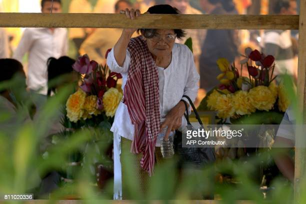 A woman looks at the grave of Cambodian critic Kem Ley during the first anniversary of his murder at his mother's home in Takeo province on July 9...