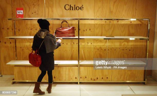 A woman looks at the last handbag left in the Chloe department inside Selfridges on Oxford Street London as the Boxing Day sales begin