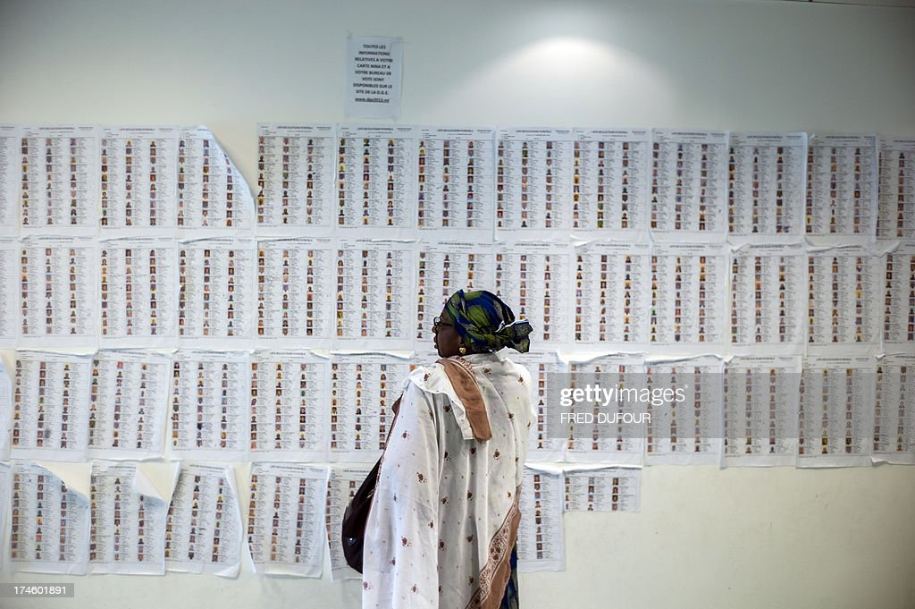 A woman looks at the list of biometric voters at the Malian consulat in Bagnolet near Paris on July 28, 2013 during the Malian presidential elections. Malians voted today for a president expected to usher in a new dawn of peace and stability in the conflict-scarred nation. They have a choice of 27 candidates as they vote for the first time since last year's military coup upended one of the region's most stable democracies, as Islamist militants hijacked a separatist uprising to seize much of the country . AFP PHOTO / FRED DUFOUR