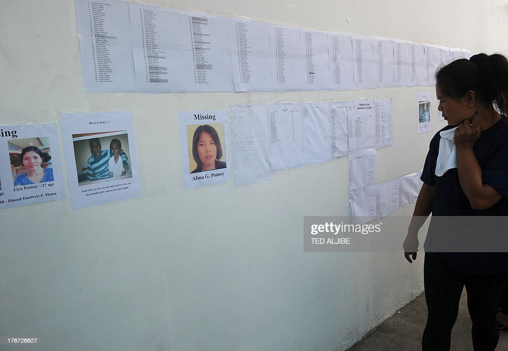 A woman looks at the list of missing passengers posted at the office of a ferry involved in a collision, in Cebu City, central Philippines on August 18, 2013. Philippine rescuers struggled in rough seas August 18, as they resumed a bleak search for 85 people missing in the country's latest ferry disaster, but insisted miracle survivor stories were possible. AFP PHOTO/TED ALJIBE