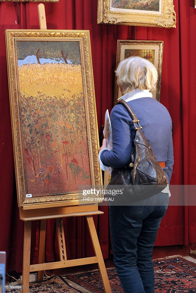 A woman looks at the oil on canvas 'Champ de blé d'or et de sarrasin' (Field of gold wheat and buckwheat) made on 1900 by French painter Paul Serusier on May 3, 2013 in Brest, Britany. The painting, which reached a record sell of 1,24 million francs (189.000 euros) for a Serusier in 2001, will go under the hammer once again on May 4.
