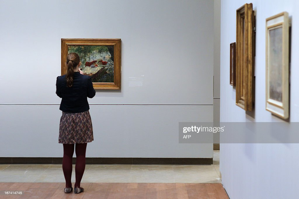 A woman looks at the painting 'Deux femmes endormies dans une barque sous les saules' by John Singer Sargent, three days before the opening of 'Normandie Impressionniste' at Caen's fine arts museum, on April 24, 2013. The exhibition which takes place in Caen is one of the three most important, with the ones of Le Havre and Rouen, which are 'National interest' labelized. Caen's exhibition gathers 67 art paintings including 34 from abroad. This exhibition (in Rouen, Caen and Le Havre) begins on April 27 to September 29.