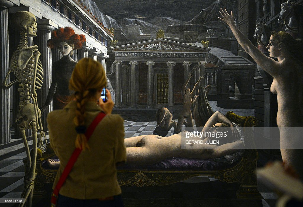 A woman looks at the painting 'La Venus endormie' by Paul Delvaux during the exhibition entitled 'Surrealism and the Dream' at the Thyssen-Bornemisza museum in Madrid, on October 7, 2013.