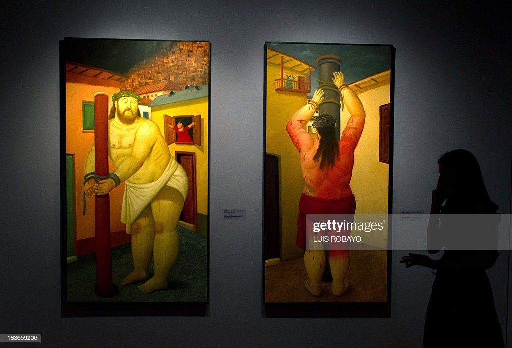 A woman looks at the paintings 'Christ at the column' (L) and 'Flagellation of Christ' of the exhibition 'Via Crucis, the passion of Christ' of Colombian artist Fernando Botero, on October 8, 2013, in Cali, department of Valle del Cauca, Colombia. Botero was the curator of his own exhibition, which is composed of 27 oil paintings and 34 drawings combining traditional aspects of Catholicism and the modern world.