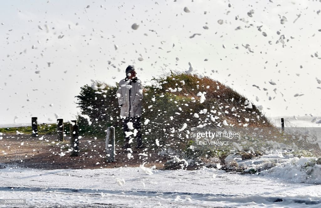 A woman looks at the sea as foam flies in Les Sables-d'Olonne, western France, on February 9, 2016. High winds buffeted northwestern Europe on February 8, leaving one woman in France in a coma after she was hit by an advertising hoarding. Electricity was cut to 5,000 homes in northern France. / AFP / LOIC VENANCE