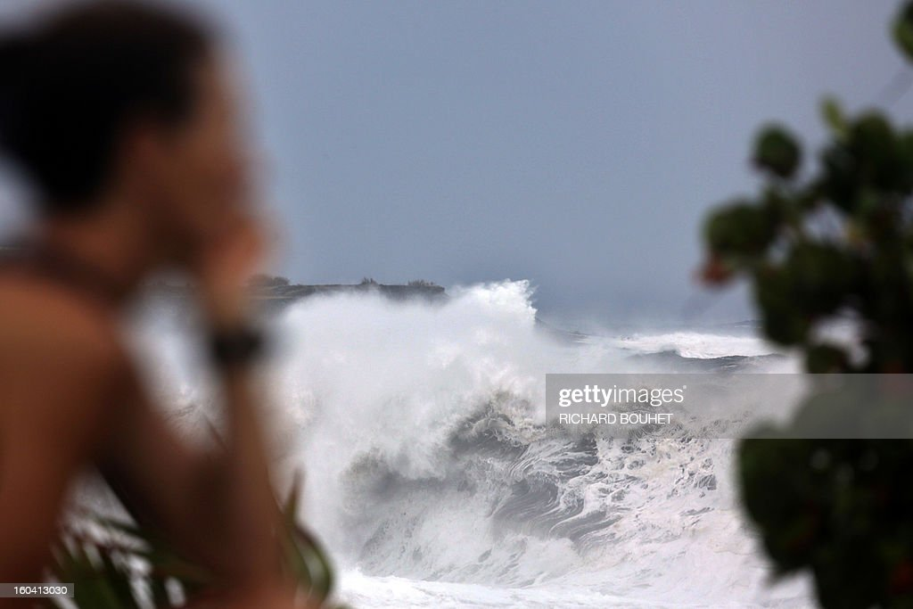 A woman looks at the sea on the northwestern coast of French Indian Ocean island of La Reunion on January 31, 2013 near Saint-Paul, as high waves hit the coastline, caused by the cyclone Felleng at 530 Km north of the island. BOUHET