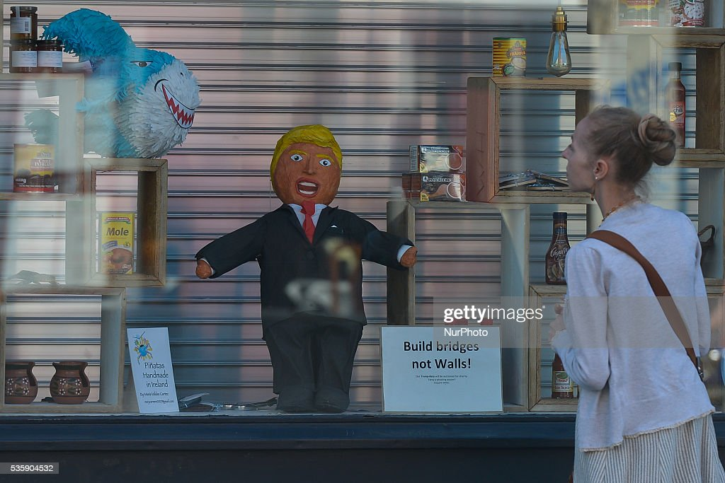 A woman looks at the shop window with Donald Trump, an American billionaire businessman, politician, television personality, author, and the presumptive nominee of the Republican Party for President of the United States in the 2016 election. On Monday, 30 May 2016, in Dublin, Ireland.