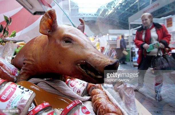 A woman looks at the shopboard with the roasted piglet at the International exhibition 'Prodexpo2014' in Minsk on November 11 2014 Food companies...