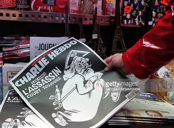 A woman looks at the special commemorative edition of French satirical newspaper Charlie Hebdo at a newsstand in Paris on January 6 to mark the...