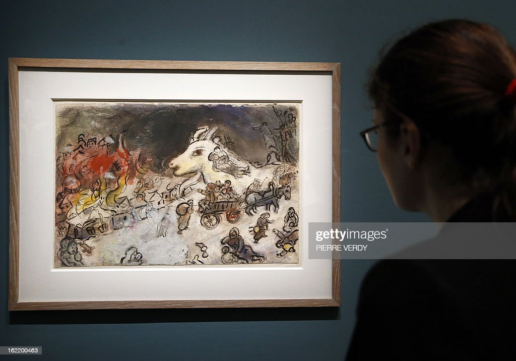A woman looks at 'The war' (1943) painting by Russian-born and naturalized French painter Marc Chagall, during an exhibition entitled 'Between war and peace', on February 20, 2013 at the Museum of Luxembourg in Paris. The event will be held from February 21 until July 21, 2013.