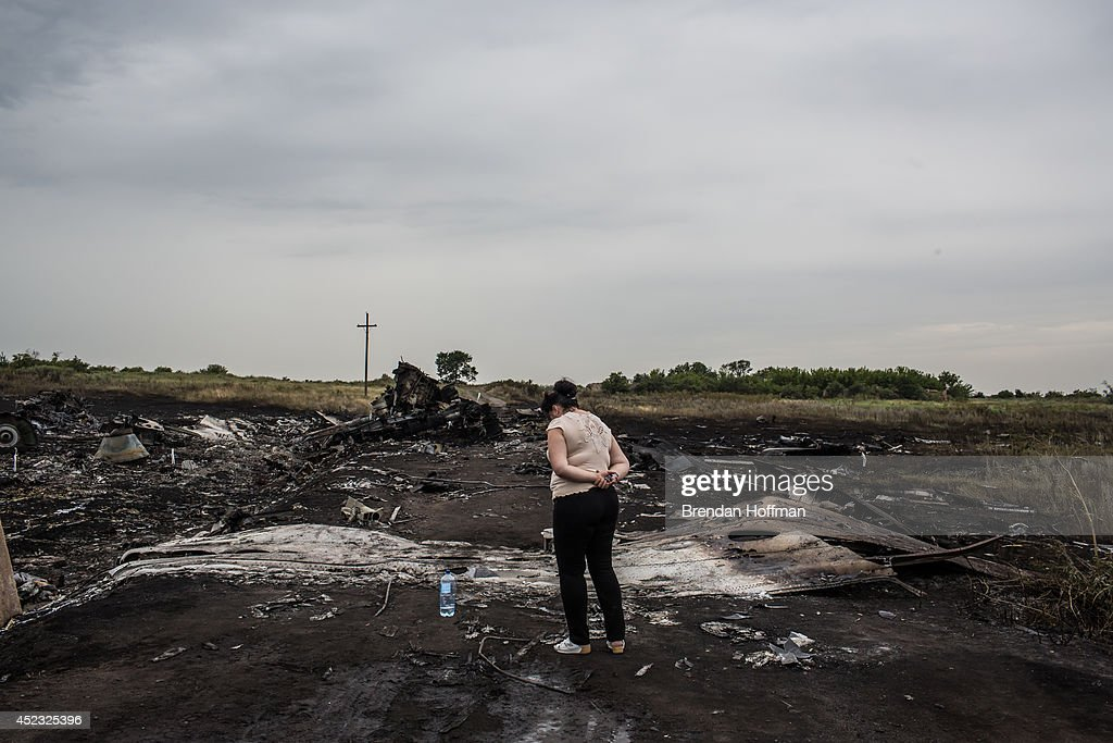 A woman looks at the wreckage of passenger plane Malaysia Airlines flight MH17 on July 18, 2014 in Grabovka, Ukraine. Malaysia Airlines flight MH17 travelling from Amsterdam to Kuala Lumpur crashed yesterday on the Ukraine/Russia border near the town of Shaktersk. The Boeing 777 was carrying 298 people including crew members, the majority of the passengers being Dutch nationals, believed to be at least 173, 44 Malaysians, 27 Australians, 12 Indonesians and 9 Britons. It has been speculated that the passenger aircraft was shot down by a surface to air missile by warring factions in the region.