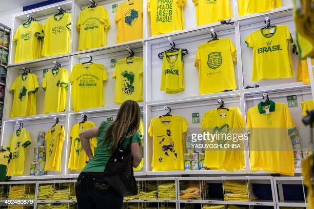 A woman looks at Tshirts for sale designed for Brazilian fans for the FIFA World Cup 2014 at a store in Rio de Janeiro Brazil on May 20 2014 40000...