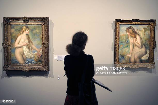 A woman looks at two paintings 'Baigneuse aux cheveux longs' 18951896 and 'Baigneuse' 1892 by French artist Pierre Auguste Renoir during the...