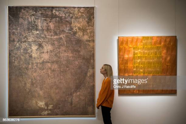 A woman looks at Untitled by Farah Moshiri and Untitled by Samir Sayegh during a press call for the India Islamic Exhibition at Sotheby's on October...