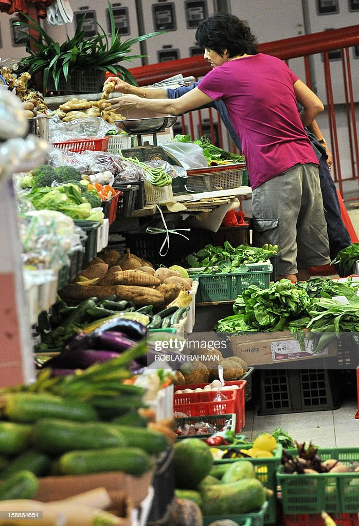 A woman looks at vegetables at a market in Singapore on January 2, 2013. Singapore's economy grew in the fourth quarter, avoiding a technical recession despite disappointing growth figures for 2012, government data showed on January 2.