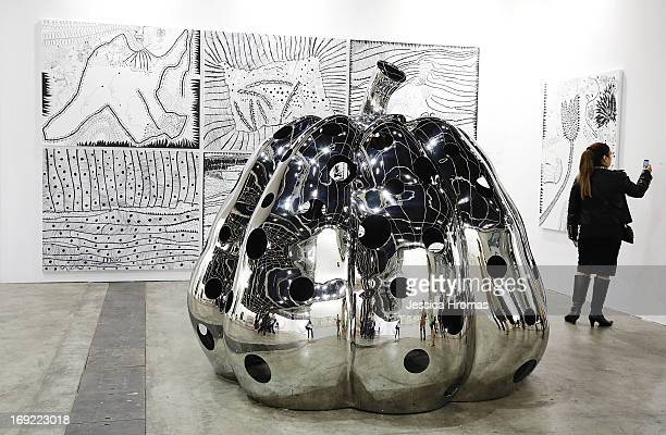 A woman looks at work by Yayoi Kusama represented by Victoria Miro London and Ota Fine Arts at Art Basel May 22 2013 in Hong Kong