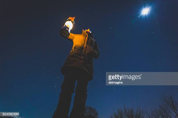 Woman looks comet in the night sky