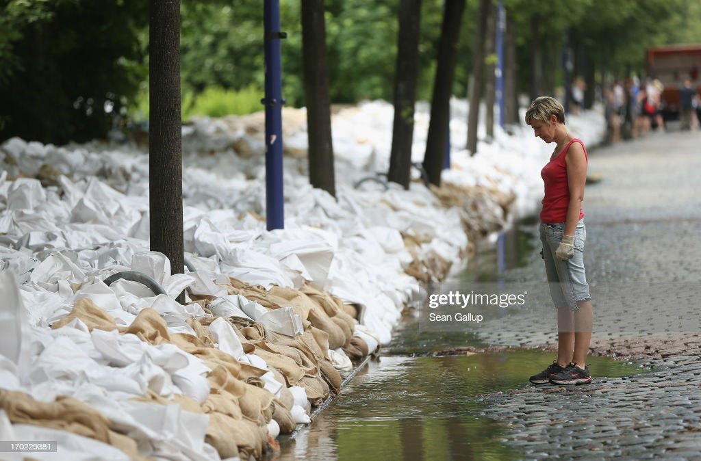 A woman looks down at water next to sandbags stacked by volunteers against rising floodwaters in the Werder district of the city center next to the swollen Elbe river on June 9, 2013 in Magdeburg, Germany. Magdeburg is enduring its highest floodwaters in its 1,200 year history and local authorities have called on 23,000 residents from outlying areas to evacuate their homes. Catastrophic flooding has hit portions of southern and eastern Germany that has left at least seven people dead and forced tens of thousands to flee their homes. Towns in northern Germany downstream from the Elbe are also bracing for floods in coming days.