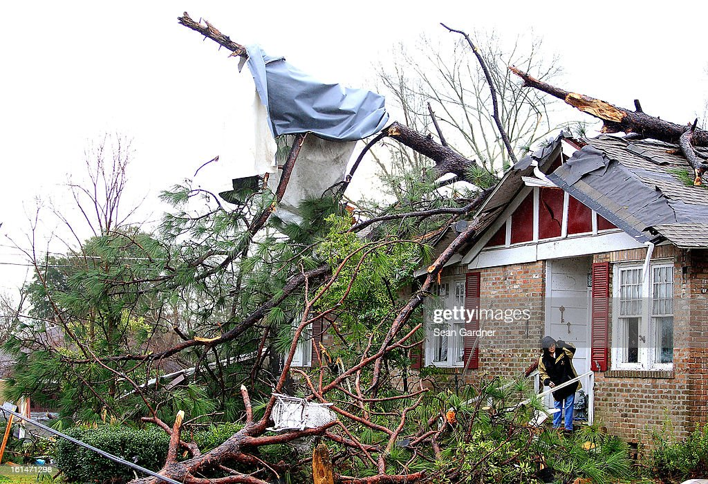 A woman looks down the street from her damaged home a day after a tornado touched down on February 11, 2013 in Hattiesburg, Mississippi. Hundreds of homes were destroyed and over sixty people injured when the tornado ripped through the town.