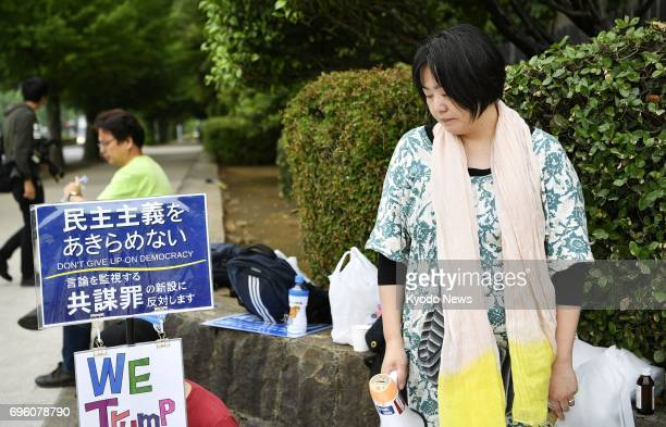 A woman looks downcast in front of the Diet building in Tokyo on June 15 after the parliament enacted contentious legislation to criminalize the...
