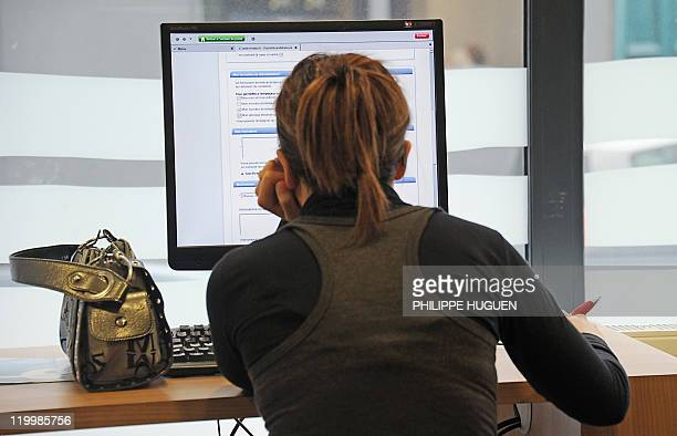 A woman looks for a job on the Pole Emploi website on July 28 2011 in the northern city of Bailleul in a Pole Emploi agency the French office...