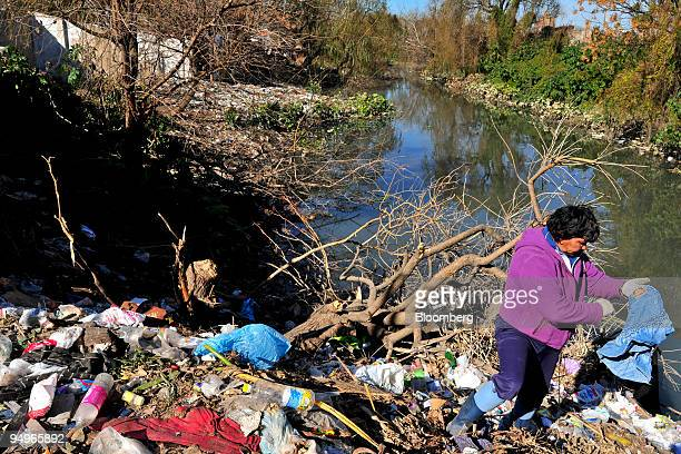 A woman looks for clothing in a pile of garbage along the banks of the Riachuelo River near Buenos Aires Argentina on July 27 2009 The World Bank in...