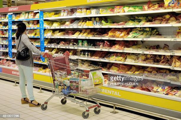 A woman looks for products as she buys groceries in an Auchan supermarket a branch of the French international retail group Auchan on June 27 in a...