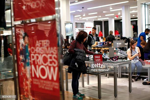 A woman looks for shoes at a Macy's store on December 24 2015 in New York City Lastminute shoppers get some of the best deals many of the major...