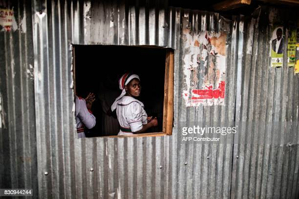 TOPSHOT A woman looks from a window as worshippers attend a prayer service of the Divine Church of Africa whose facade had been decorated with...