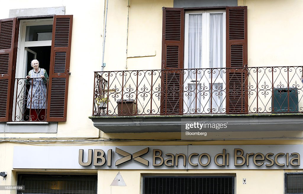 A woman looks from the window of a residential apartment above a Banco di Brescia bank branch, a subsidiary of Unione di Banche Italiane SCPA (UBI Banca), in Ronciglione, Italy, on Monday, March 11, 2013. Intesa Sanpaolo SpA and UniCredit SpA are among Italian banks due to report losses for the fourth quarter this week, as the economic contraction meant more clients failed to repay their debts. Photographer: Alessia Pierdomenico/Bloomberg via Getty Images