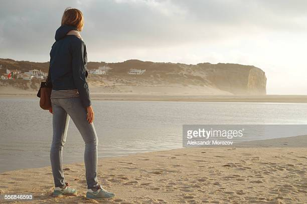Woman looks into the distance at the sunset