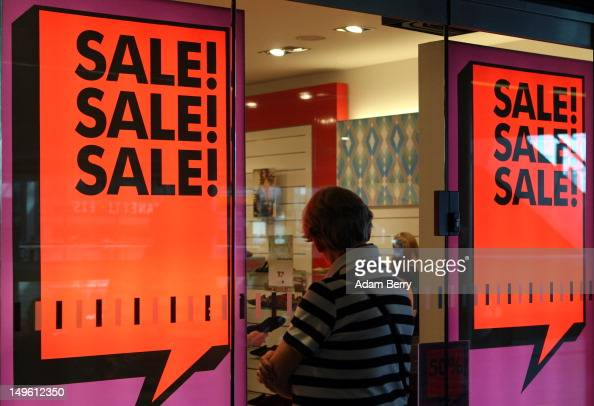 A woman looks into the window of a store advertising summer sales on August 1 2012 in Berlin Germany German retailers began their annual summer...