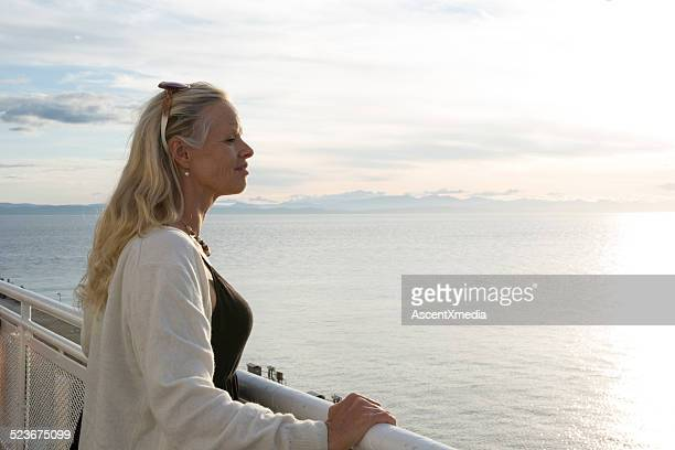 Woman looks off from deck of ship, at sea