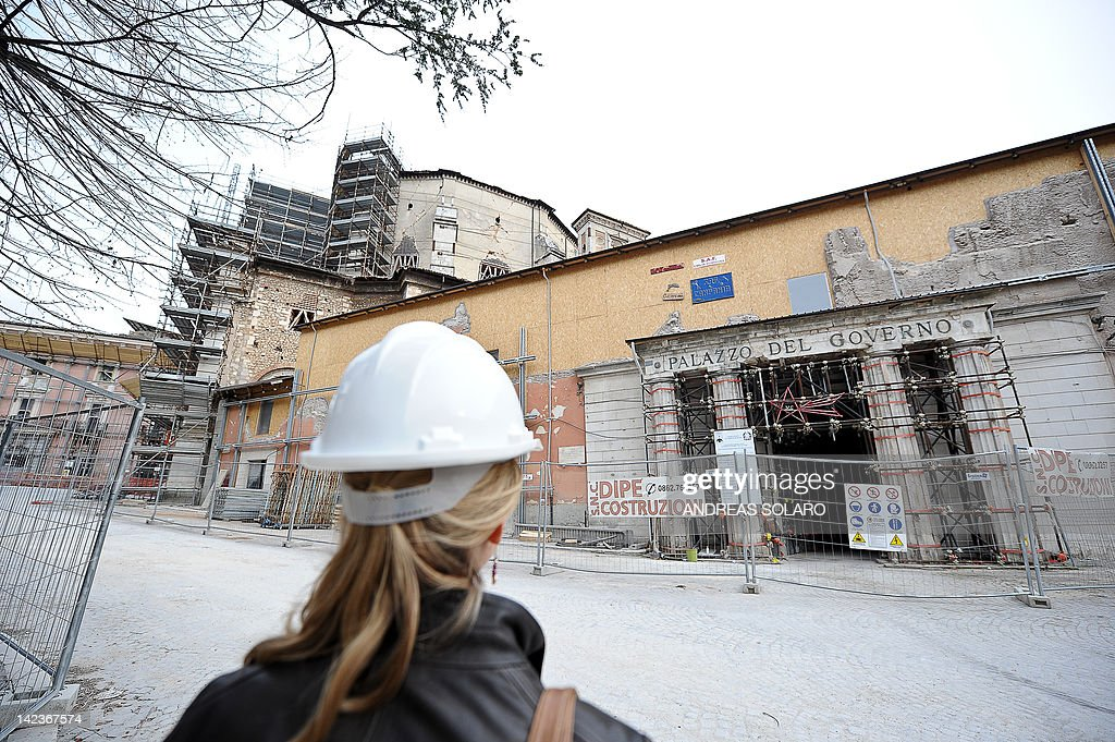 A woman looks on April 2 2012 at the remains of the government building in the 'red zone' closed to public in the historic area of L'Aquila...