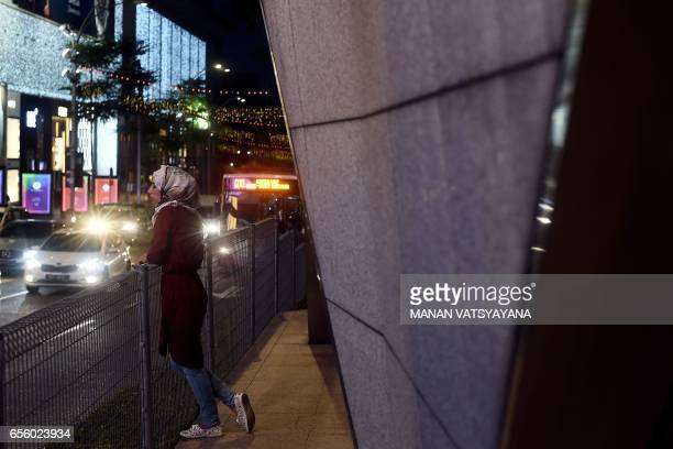 A woman looks on as evening traffic drives past in the popular Bukit Bintang tourist spot of Kuala Lumpur on March 21 2017 / AFP PHOTO / Manan...