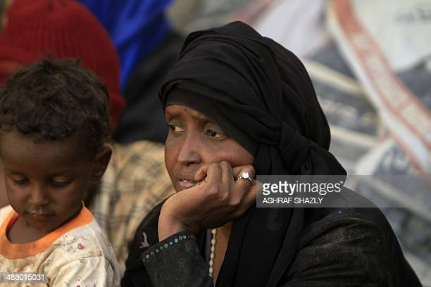 A woman looks on as illegal migrants who were abandoned in the desert by human traffickers wait at a military building in the northern Sudanese city...