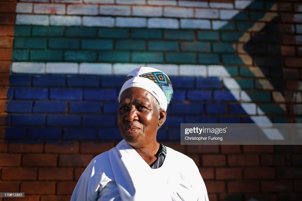 A woman looks on as members of the Church of Nazareth take part in a service at Rockville School, in Soweto on June 15, 2013 in Johannesburg, South Africa. The Baptist church, which is a mixture of Zulu tradition and Christianity, continued their daily life as the former South African President and leader of the anti-apartheid movement who is spending a seventh night in hospital. It has been reported that he is responding better to treatment for a recurring lung infection.