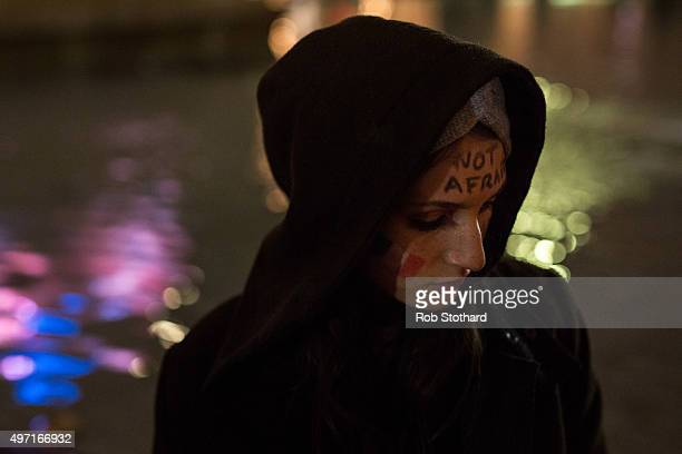 A woman looks on as people hold a vigil for victims of the Paris terrorist attacks in Trafalgar Square on November 14 2015 in London England Several...