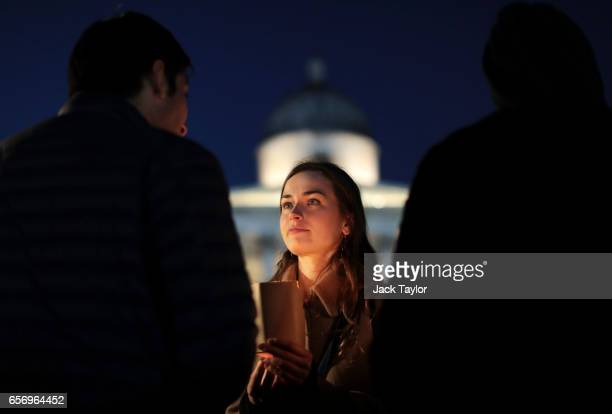 A woman looks on as people light candles during a candlelit vigil at Trafalgar Square on March 23 2017 in London England Four People were killed in...