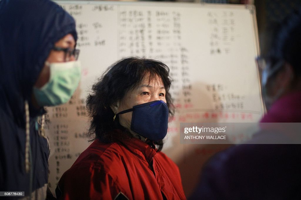 A woman looks on as she stands in front of a board showing details of missing people and successful rescues during a rescue operation at the site of a collapsed building in the southern Taiwanese city of Tainan early on February 7, 2016 following a strong 6.4-magnitude earthquake. More than 250 people have been rescued from the Wei-kuan apartment complex in the southern city of Tainan since the quake hit at 4:00 am Saturday, killing 14 people and toppling four blocks of around 100 homes in total. WALLACE