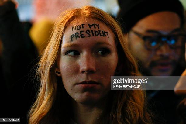 A woman looks on as she takes part in a protest against Presidentelect Donald Trump in front of Trump Tower in New York on November 10 2016 / AFP /...